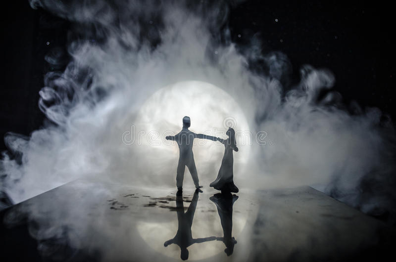 Silhouettes of toy couple dancing under the Moon at night. Figures of man and woman in love dancing at moonlight. With fog stock image