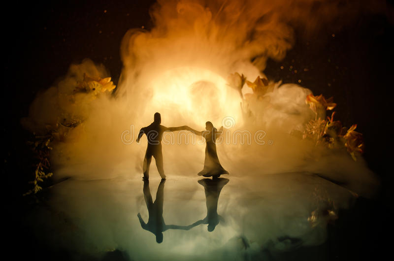 Silhouettes of toy couple dancing under the Moon at night. Figures of man and woman in love dancing at moonlight royalty free stock images