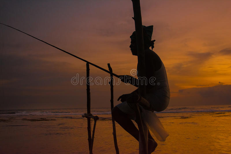 Silhouettes of the traditional Sri Lankan stilt fishermen. At the sunset in Weligama, Sri Lanka. Stilt fishing is a method of fishing unique to the island stock images