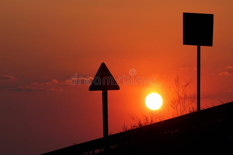 Silhouettes of traffic signs against the red sun at sunset.  royalty free stock photography