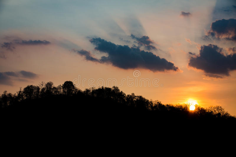 Silhouettes of trees and mountain on sunset royalty free stock photo