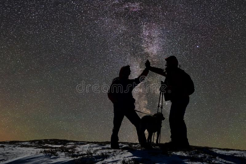 Silhouettes of two adult male skiers with dog on top of snow-covered mountain at night. Dark starry sky on background stock photography