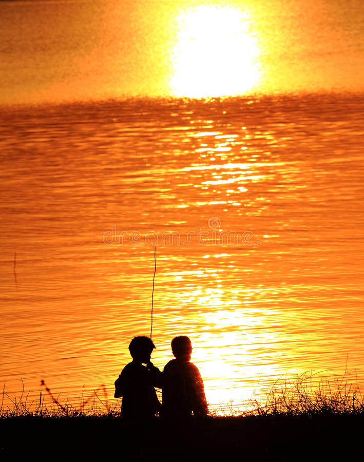 Silhouettes of two children playing on the beach a. T sunset royalty free stock images