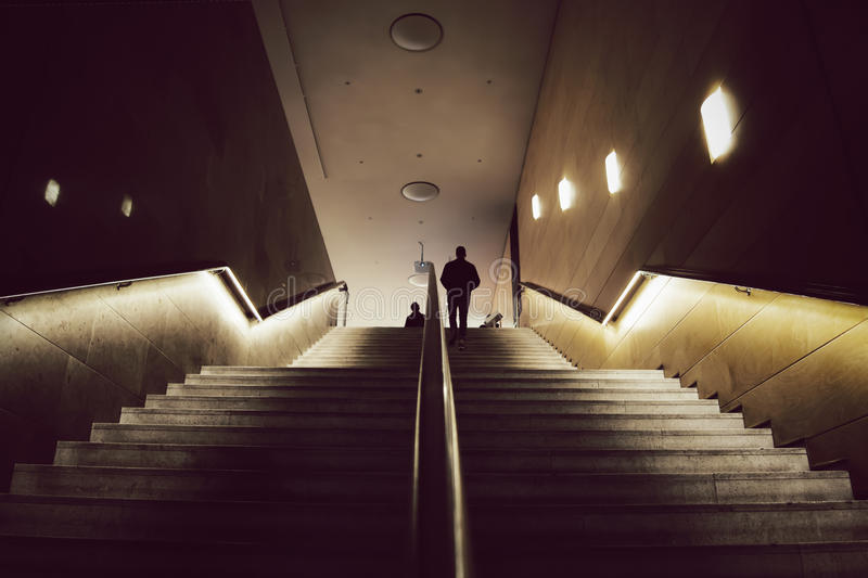 Silhouettes of two men meeting on top of mysterious wide stairs. Silhouettes of two man meeting on top of a mysterious, golden lit staircase. Low perspective stock photos