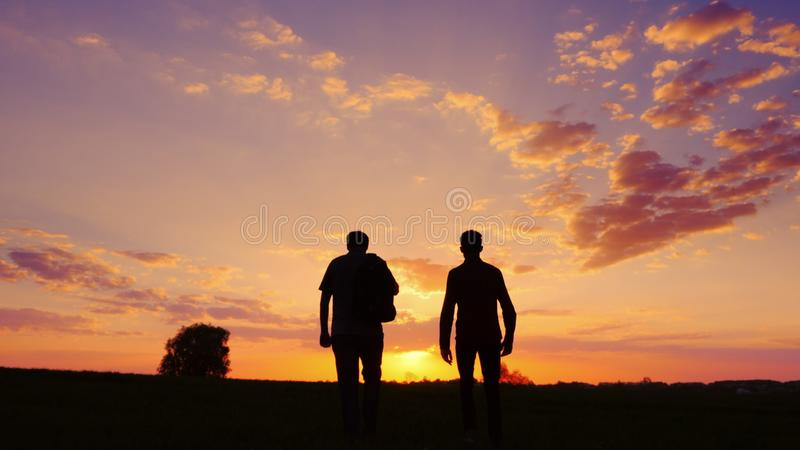 Silhouettes of two men - son and father go together to meet the sunset. Back view. royalty free stock photo