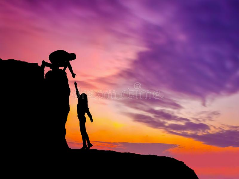 Silhouettes of two people climbing on mountain and helping stock photos