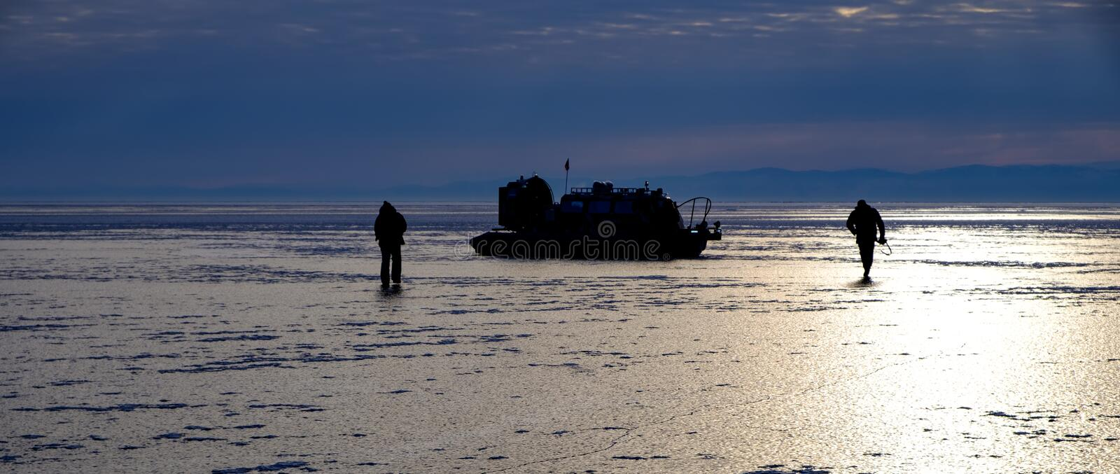 Silhouette of two people and hovercraft boat on the ice stock images