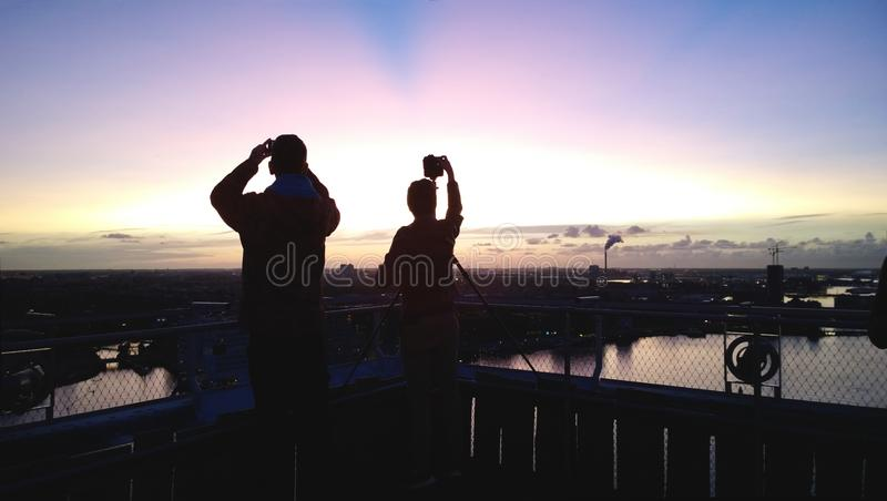 Silhouettes of two people at sunset. People take photographs of a beautiful sunset from a tall building. royalty free stock photo