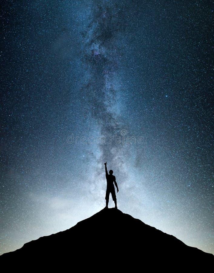 Silhouettes of winner on mountain peak stock image