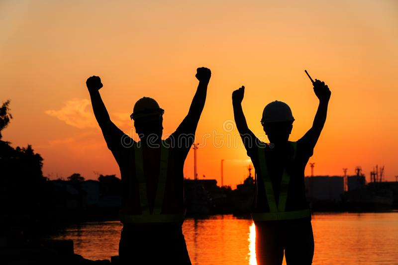 Silhouettes of worker and engineer Raising the hand up and standing on the shipyard. Background is oil storage silo. Teamwork stock image