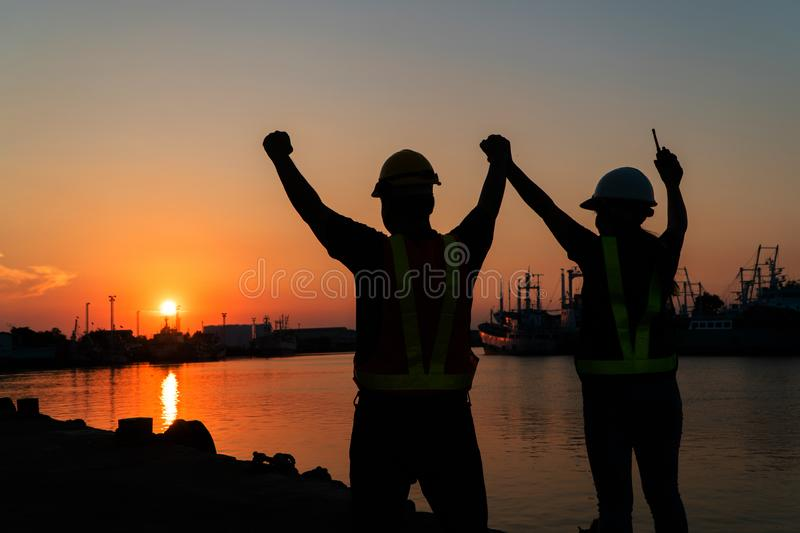 Silhouettes of worker and engineer Raising the hand up and standing on the shipyard. Background is oil storage silo. Teamwork royalty free stock images