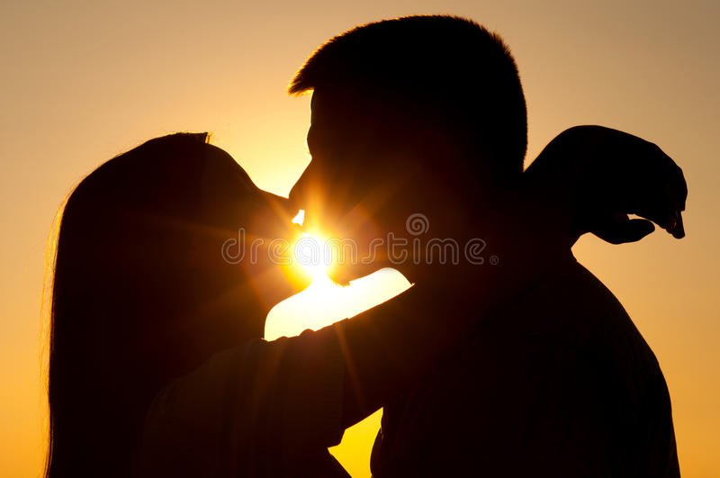 Silhouettes of young couple kissing stock image