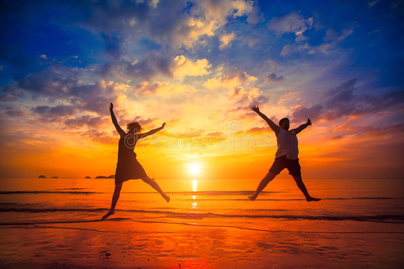 Silhouettes of young people jumping at sunset on the sea beach. Happy. royalty free stock images