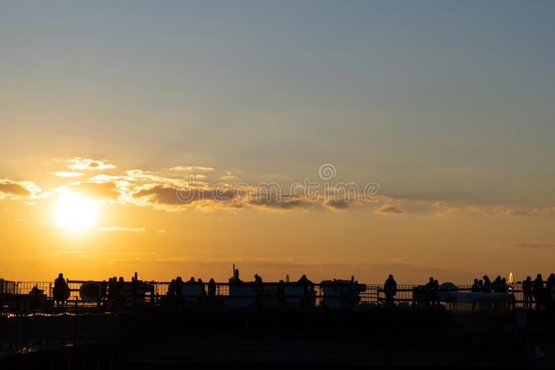 Silhouettes of young people sitting on the St. Petersburg roof against the background of the orange sunset.  stock images