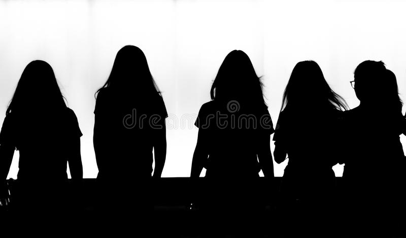 Silhouettes of young  women walking in motion blur in the night stock photography