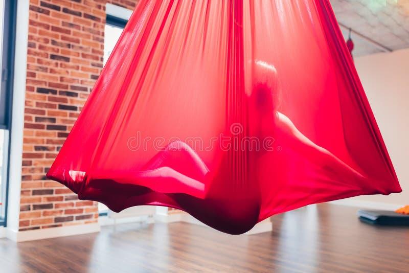 Silhouettez de détendre la fille mince complètement cachée par l'hamac rouge dans la classe de yoga images libres de droits