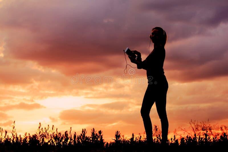 Silhouettez l'étudiante écoutant la musique d'un comprimé photo stock