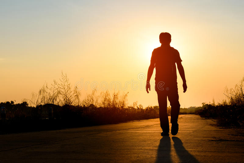 Silhouettez l'homme marchant sur la route au fond de coucher du soleil images libres de droits
