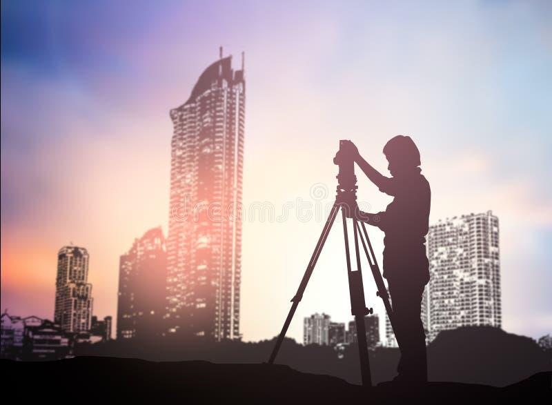 Silhouettez l'ingénieur d'enquête travaillant dans un chantier au-dessus de tache floue photo libre de droits