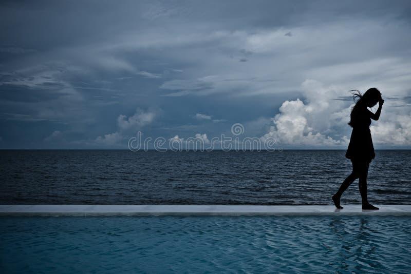 Silhouettez l'ombre des femmes établissant avec l'océan de mer images stock