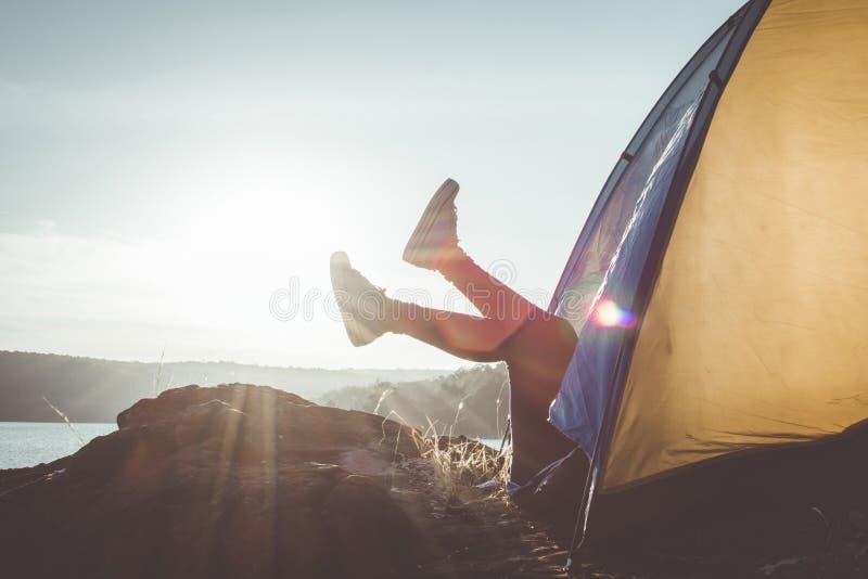 Silhouettez la femme de pieds détendant dans la tente pendant le camping images stock
