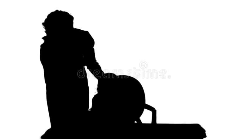 Silhouettez la fille de aide de maman avec de la matte de voie de travail images stock