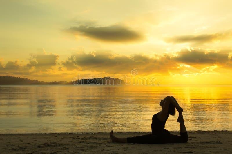 Silhouettez la fille de yoga au lever de soleil sur la plage photographie stock