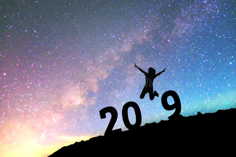 Silhouettez la jeune femme heureuse pour le fond de la nouvelle année 2019 sur le Th image stock