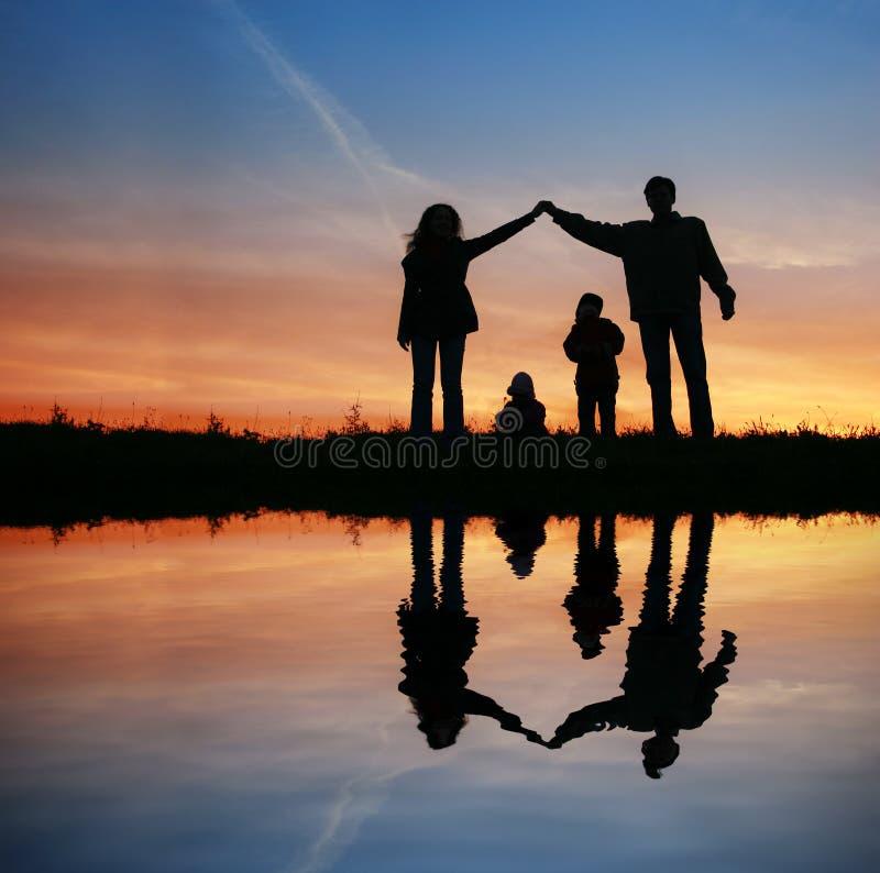 Silhouettez la maison de famille sur le coucher du soleil