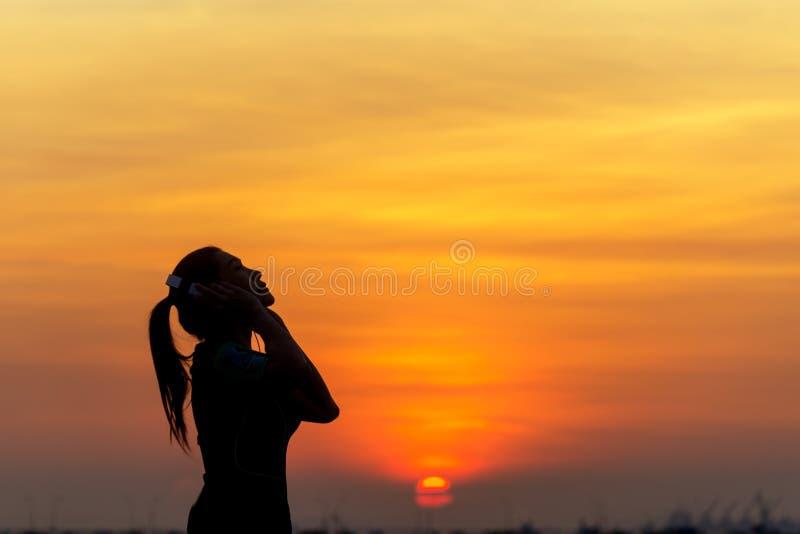 Silhouettez la musique de écoute de coureur de femmes et la liberté se sentante, heureux et en appréciant le sunse de nature photos libres de droits