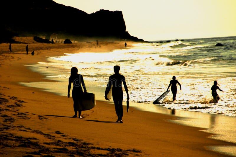 Silhouettez la promenade de plage photographie stock libre de droits