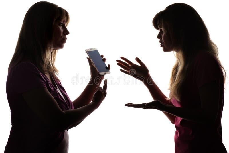 Silhouettez la querelle des parents et des adolescents dus aux réseaux sociaux, smartphone photo libre de droits