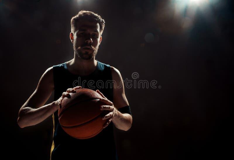 Silhouettez la vue d'un joueur de basket tenant la boule de panier sur le fond noir photos stock