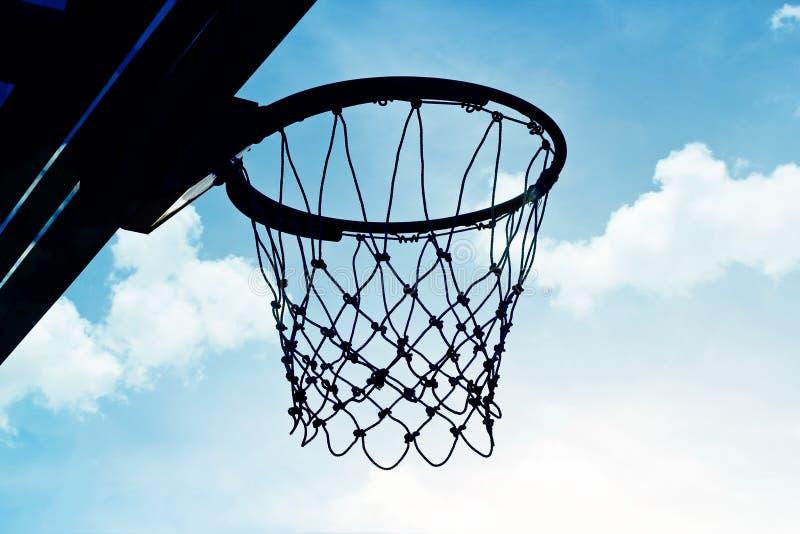Silhouettez le cercle de basket-ball dehors dans le nuage et le ciel bleu photo libre de droits
