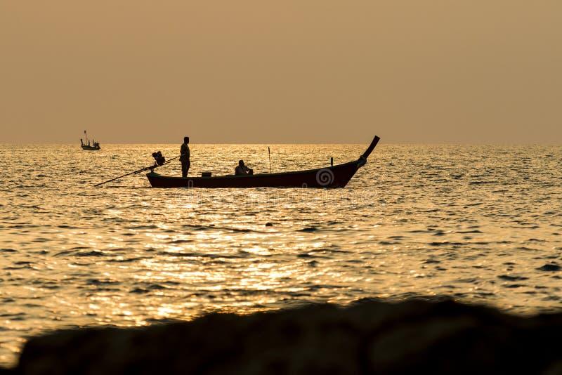 Silhouettez le ciel de coucher du soleil de l'homme sur le bateau phuket Thaïlande de longue queue photo libre de droits