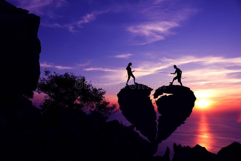Silhouettez le concept de fond de Valentine, couples tirant la corde sur la pierre en forme de coeur cassée image libre de droits