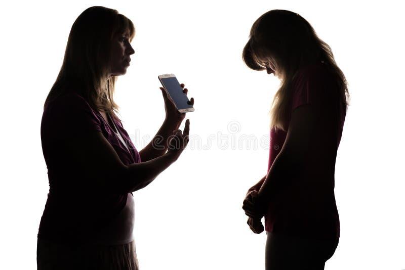 Silhouettez le conflit des parents et des adolescents dus au divertissement électronique photo stock