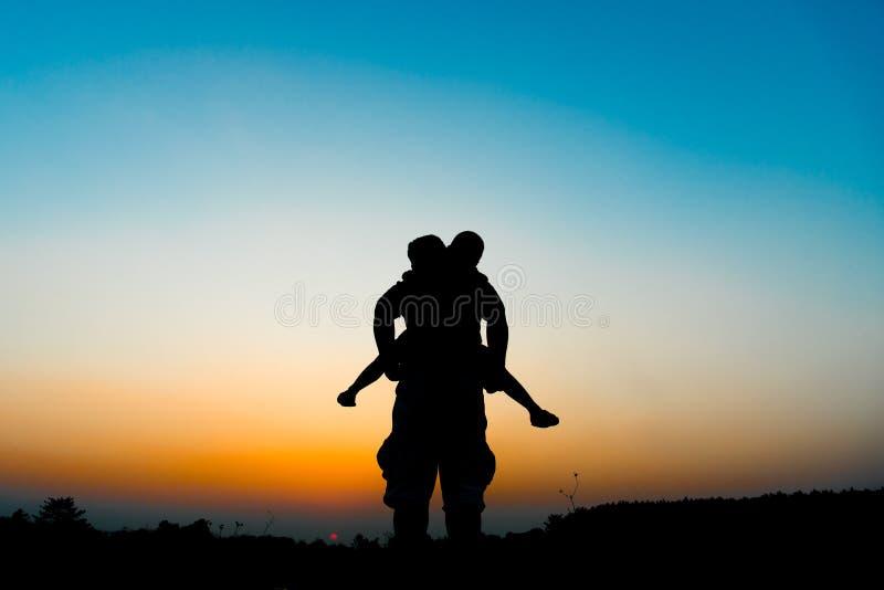 Silhouettez le fils monte son cou du ` s de père photos libres de droits