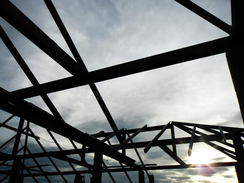 Silhouettez le fond avec le ciel bleu, structure du cadre en acier de toit pour la construction de construction de toit image stock