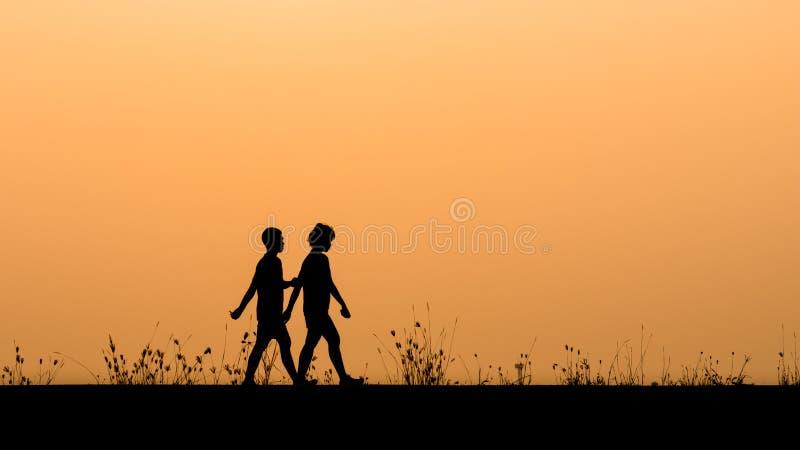 Silhouettez le garçon et la fille marchant sur le fond de coucher du soleil photos libres de droits