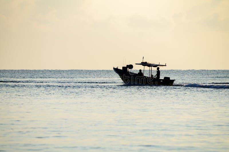 Silhouettez le pêcheur traditionnel allant pêcher des poissons au début de la matinée avec son bateau image stock