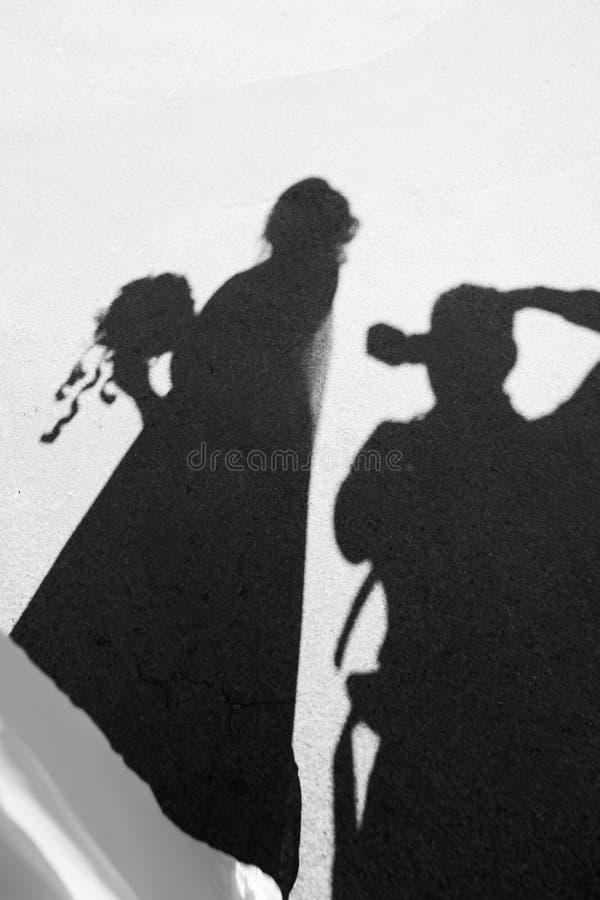 Silhouettez le photographe sur le trottoir qui photographie la jeune mariée image stock
