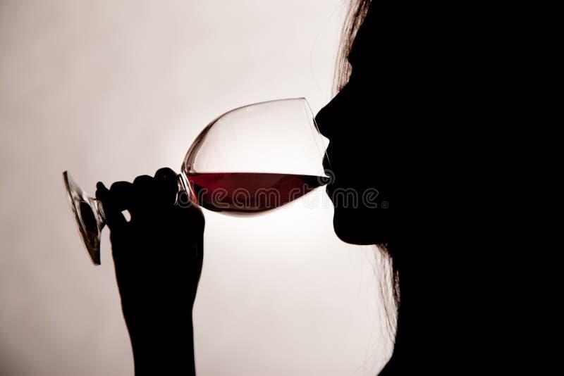 Silhouettez le tir d'une femelle buvant du vin rouge photos stock