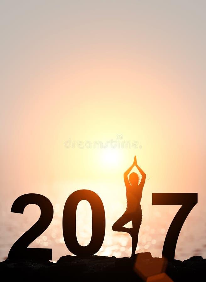 Silhouettez le yoga de femme de l'Asie dans le tex 2017 de bonne année photographie stock
