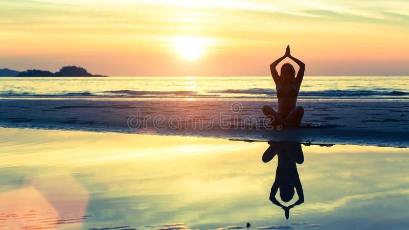 Silhouettez le yoga de pratique de femme sur la plage au coucher du soleil images libres de droits