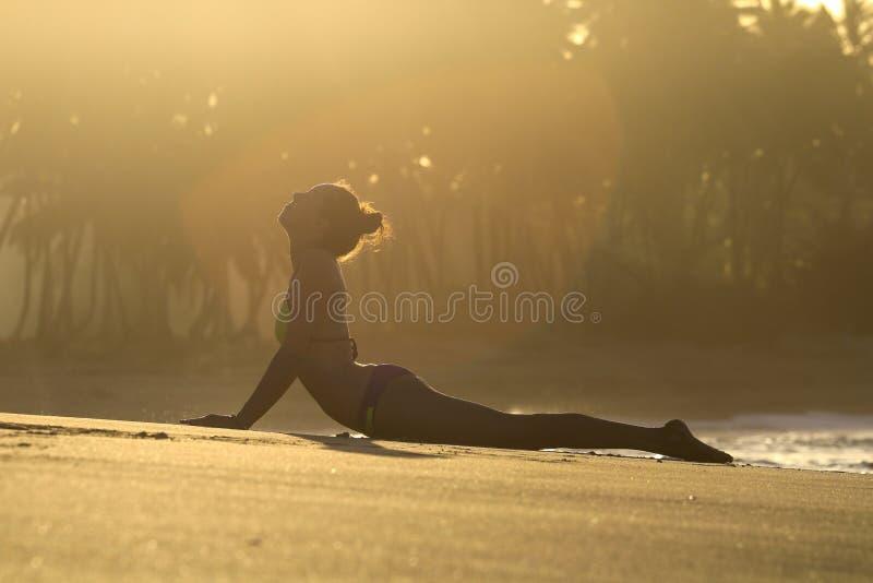 Silhouettez le yoga de pratique de jeune femme sur la plage au coucher du soleil photographie stock libre de droits
