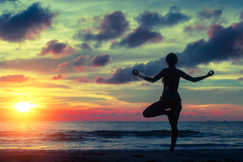 Silhouettez le yoga de pratique de jeune femme sur la plage au coucher du soleil image stock