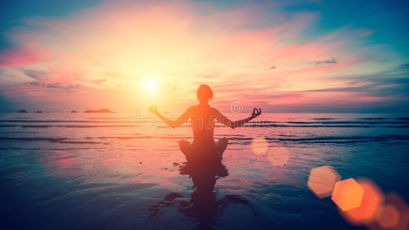 Silhouettez le yoga de pratique de jeune femme sur la plage de mer images libres de droits