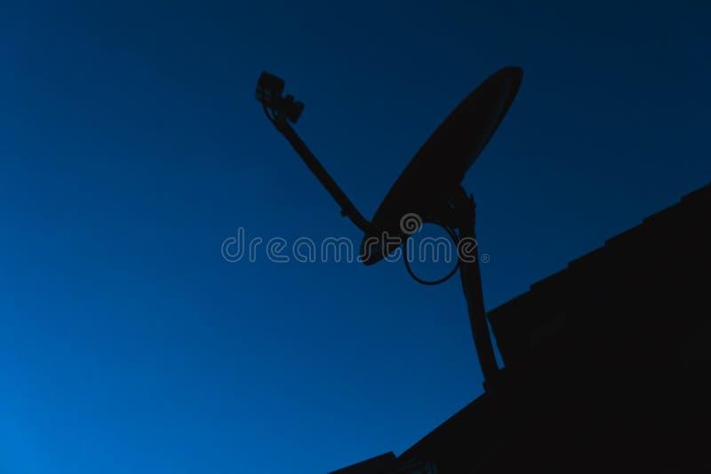Silhouettez les antennes à la maison de Digital TV d'antenne parabolique sur le bleu image libre de droits