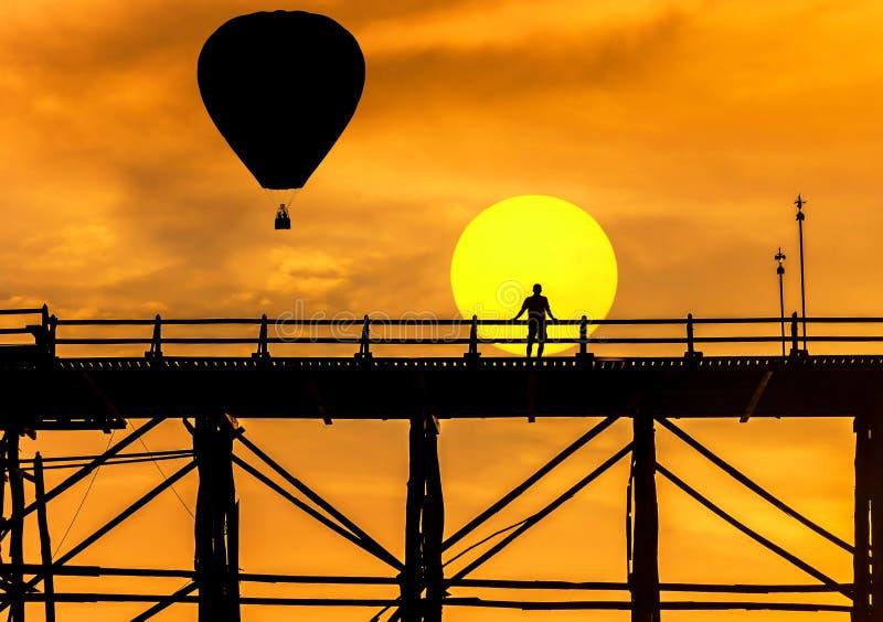 Silhouettez les ballons à air chauds flottant au-dessus du vieux pont en bois dans le sangklaburi, Thaïlande sur le coucher du so image libre de droits